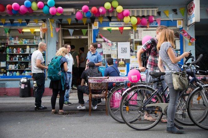 Menschen die vor einem Kiosk stehen und sich unterhalten. Zwei Menschen laufen mit Fahrrädern vorbei.