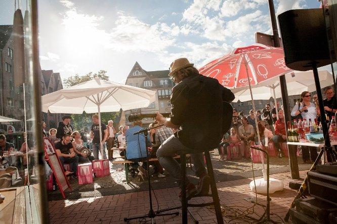 Sänger der vor vielen Leuten auf der Bühne sitzt, singt und Gitarre spielt.