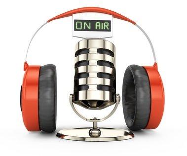 """Mikrofon mit der Aufschrift """"on Air"""" und Kopfhörern darüber"""