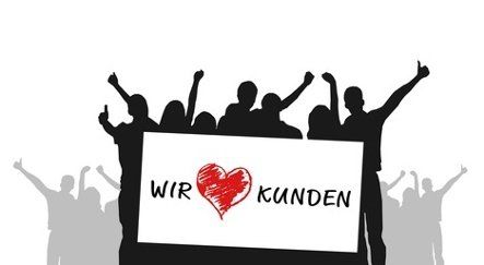 Menschen halten ein Schild mit der Aufschrift: Wir Kunden und einem Herz in der Mitte