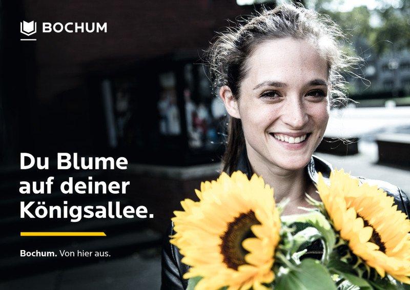 Frau mit Sonnenblumen in der Hand und der Überschrift: Du Blume auf deiner Königsallee