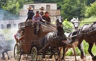 Postkutsche mit Pferden wird von anderen Cowboys auf Pferden verfolgt