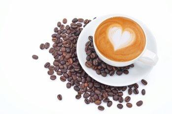 Tasse Kaffee mit einem Herzen aus Milch und Kaffeebohnen herum