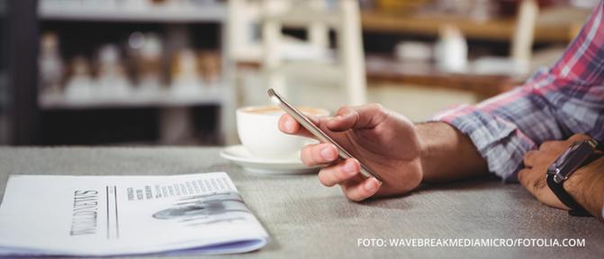 Man sitzt mit Kaffee und einer Zeitung am Tisch und liest etwas auf seinem Smartphone
