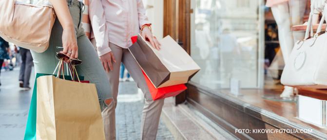 Zwei Frauen stehen mit Einkaufstaschen vor einem Schaufenster