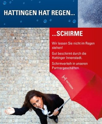 Faltblatt der Stadt Hattingen: Eine Frau hält einen Regenschirm und schaut in den Himmel in die Kamera. Falltblatt hat aufschrifft Hattingen hat Regen... ... Schirme