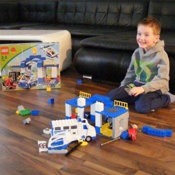 Ein Kind, das vor einem Haufen Spielsteine sitzt.