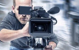 Ein Mann der eine Kamera hällt.