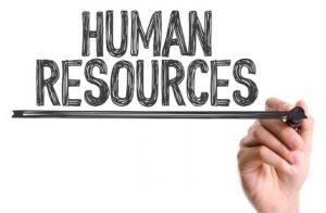"""Eine Hand die mit einem schwarzen Stift """"Human Ressources"""" schreibt und dies schwarz unterstreicht."""