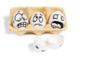 Drei Eier die in einem Eierkarton liegen, und aufgemalte geschockte Gesichter haben. Davor ein kaputtes Ei