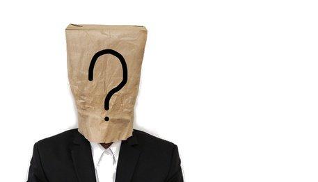 Person mit einer Tüte auf dem Kopf auf der ein großes Fragezeichen drauf gemalt ist