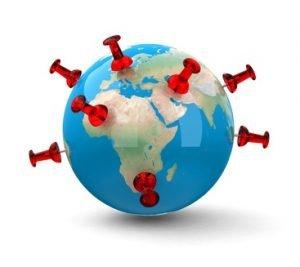 Eine Weltkugel in der mehrere rote Stecknadeln stecken