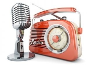 Ein älteres Modell eines Radios, vor dem ein älteres Modell eine Mikrofons steht.