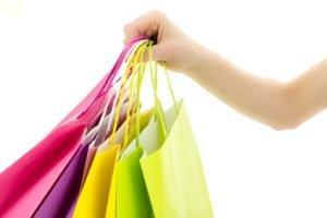 Eine Hand die vier bunte Einkaufstaschen hält.
