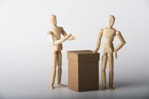 Zwei Holzfiguren die an einem Stehtisch zusammen stehen