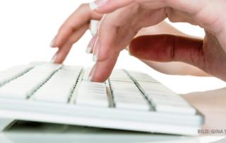 Person tippt etwas auf einer Tastatur ein