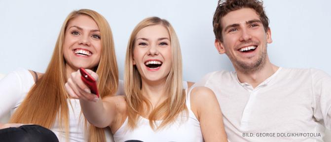 Drei Personen die Fernsehen gucken und lachen
