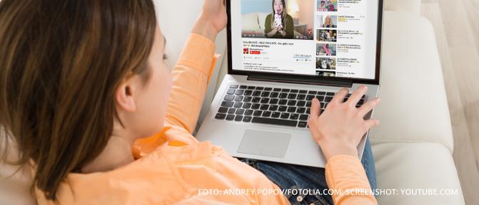 Person sitzt am Laptop und guckt ein Video bei YouTube