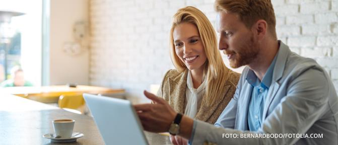 Eine Frau und ein Mann sitzen zusammen vor einem Laptop und diskutieren über etwas