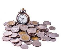 Ein Haufen Geldmünzen und eine Taschenuhr