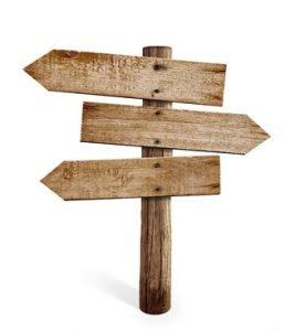 Drei Holzschilder die in unterschiedliche Richtungen zeigen