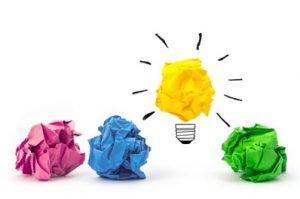 Vier bunte zerknüllte Papierbälle, ein gelber schwebt in der Luft und stellt eine Glühbirne dar