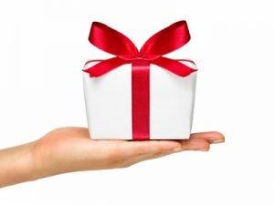 Hand die ein weißes Geschenk mit roter Schleife hält