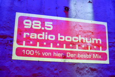 Das Radio Bochum-Logo wird an die Wand projiziert. Foto: Westfunk