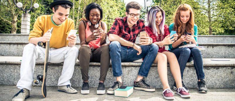 Junge Leute sitzen auf einer Stufe und surfen am Smartphone.