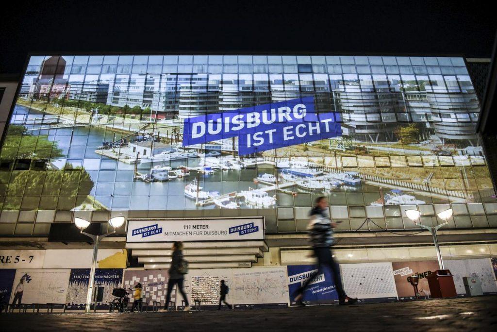 Duisburg ist echt … nicht zu übersehen: Zum offiziellen Start der Imagekampagne wurden Fotos und Videos zur neuen Wort-Bild-Marke auf die Fassade der ehemaligen Zentralbibliothek projiziert. Unterhalb der 600 Quadratmeter großen Bildfläche konnten sich die Zuschauer auf einer 111 Meter langen Interaktionswand kreativ austoben.